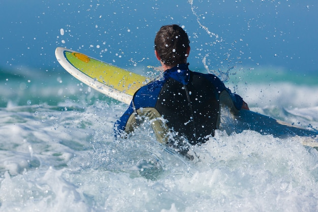 Surfista e tavola in mare con le onde