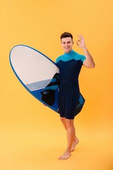 Surfista felice che cammina con la tavola da surf e che mostra il segno giusto