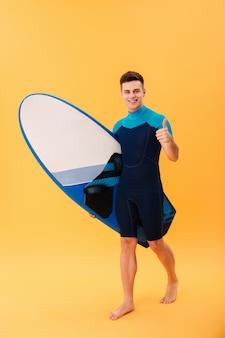 Surfista felice che cammina con la tavola da surf e il pollice in su
