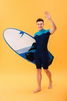 Surfista felice che cammina con la tavola da surf