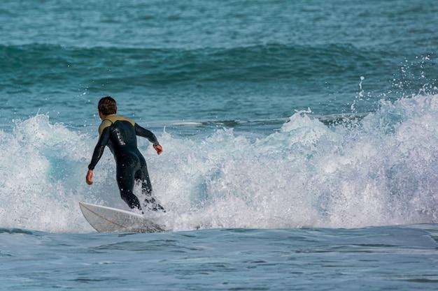 Surfista in mare con tavola e ritorno