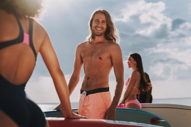 Surfista lungo dei capelli sulla macchina fotografica che posa alla spiaggia.