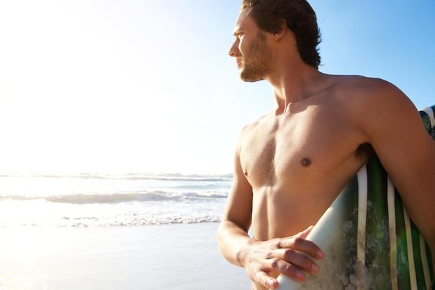 Surfista maschio che trasportano tavola da surf in spiaggia