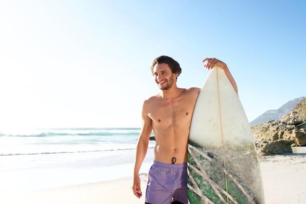 Surfista maschio felice che sta con il suo bordo alla spiaggia