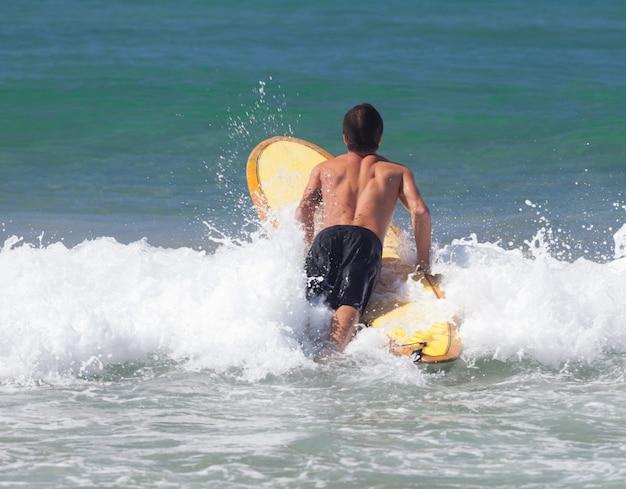 Surfista su longboard cavalca un'onda nel mare