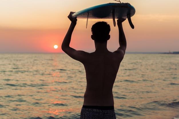 Surfista tenendo la sua tavola da surf e alla ricerca di onde