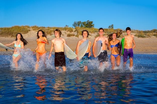 Surfisti della spiaggia del gruppo dei surfisti che spruzzano