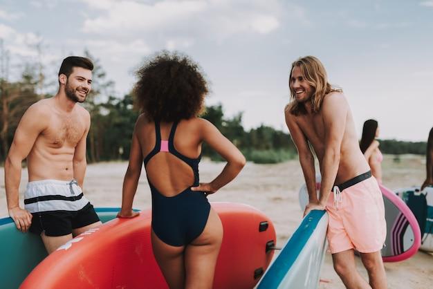 Surfisti maschii e femminili che parlano alla spiaggia. giorno festivo