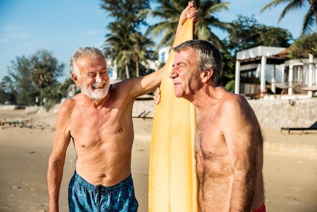 Surfisti maturi in spiaggia