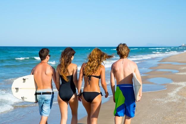 Surfisti ragazzi e ragazze a piedi vista posteriore sulla spiaggia