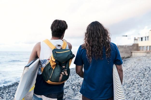 Surfisti sulla riva rocciosa di una spiaggia a guardare un tramonto
