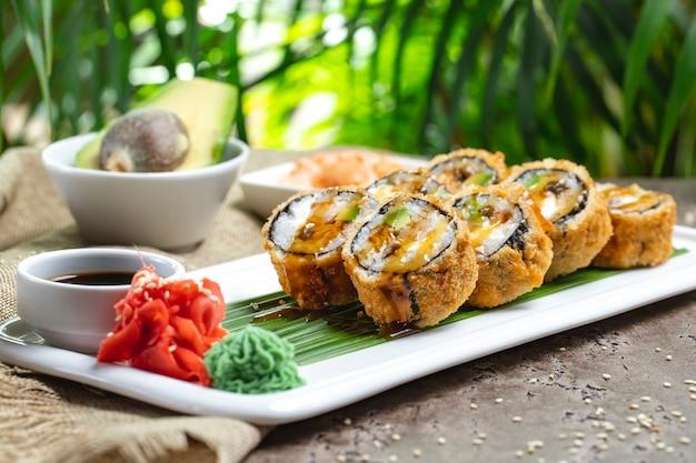 Sushi al forno con salsa wasabi, zenzero e soia su una foglia di bambù