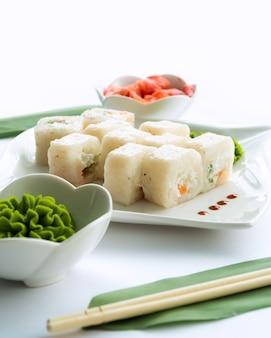 Sushi bianchi su un piatto bianco e superficie bianca con wasabi, zenzero e porcini
