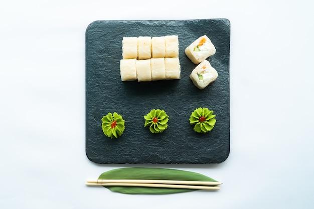 Sushi bianchi su una superficie nera e superficie bianca con wasabi e chopstocks