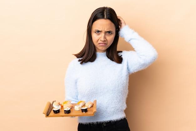 Sushi castani della tenuta della donna della giovane corsa mista