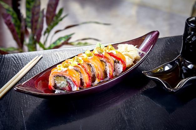 Sushi del rotolo giapponese di cucina moderna con crema di formaggio e salmone. primo piano vista su sushi con avocado e salmone. frutti di mare sani. pesce. dieta, cibo equilibrato. copia spazio. cucina giapponese