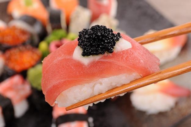 Sushi di tonno con caviale tenuto da bacchette