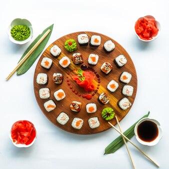 Sushi diversi su una superficie rotonda in legno con salsa di soia, zenzero, wasabi e bacchette