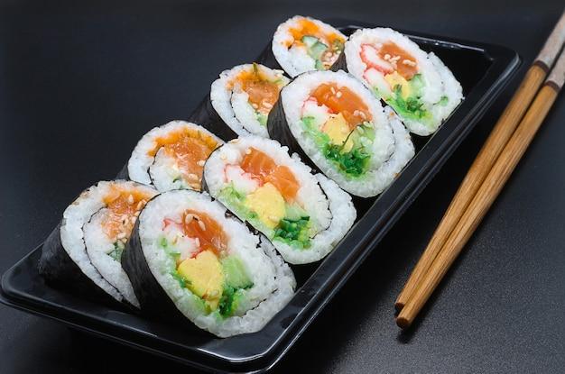 Sushi e bacchette sul tavolo scuro