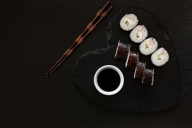 Sushi giapponese con salsa di soia sul piatto nero a forma di cuore con le bacchette.