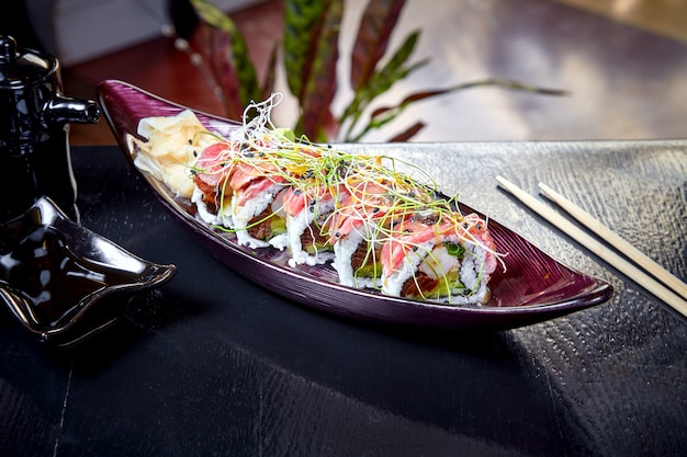 Sushi giapponesi del rotolo di cucina moderna con gamberetto e arrosto di manzo. primo piano vista su sushi con avocado e salmone. frutti di mare sani. pesce. dieta, cibo equilibrato. copia spazio. cucina giapponese