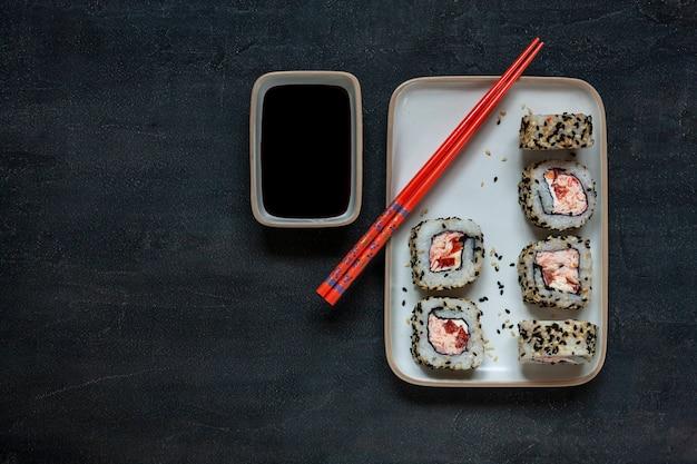Sushi giapponesi della mousse della polpa di granchio con la salsa di soia sopra con le bacchette