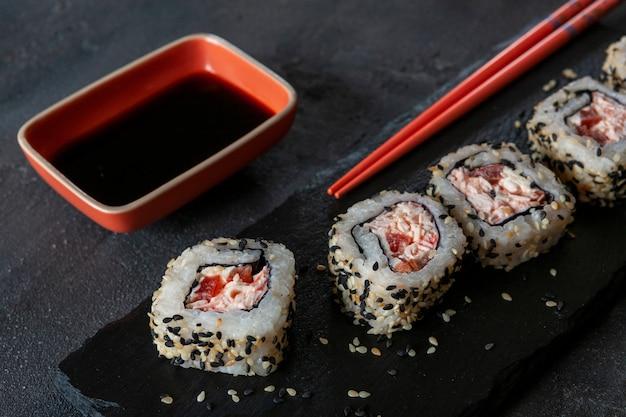 Sushi giapponesi della mousse della polpa di granchio con la salsa di soia sul bordo di pietra con le bacchette