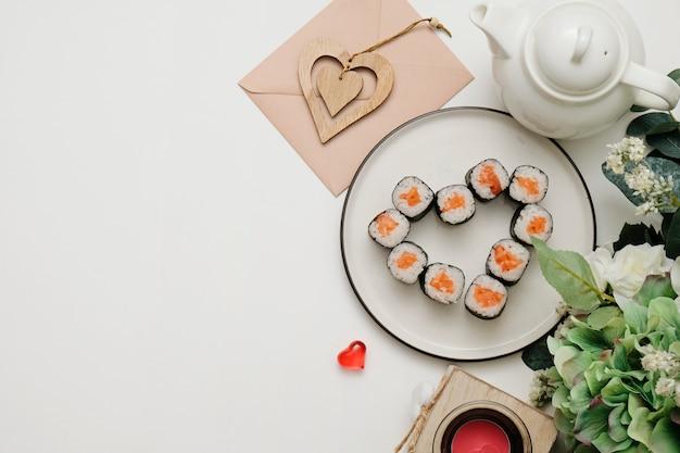Sushi per san valentino - rotolare a forma di cuore, sul piatto sopra. disteso