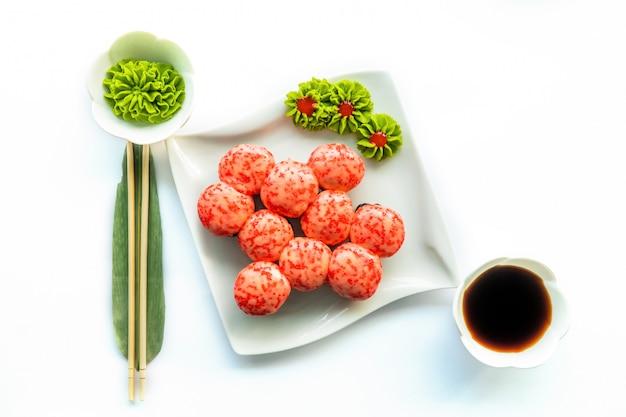 Sushi rossi su un piatto bianco e superficie bianca con wasabi e chopstocks