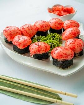 Sushi rossi su un piatto bianco e superficie bianca con wasabi, zenzero e chopstocks