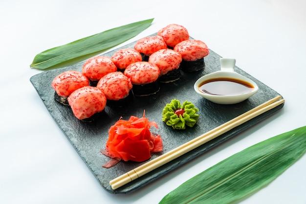 Sushi rosso su una superficie nera e una superficie bianca con wasabi, zenzero, salsa di soia e bacchette