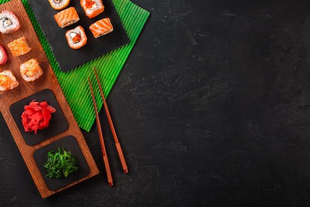 Sushi set con wasabi e zenzero sul vassoio di pietra nera sul tavolo nero. vista dall'alto