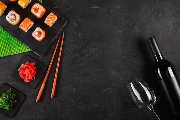 Sushi set di sashimi e involtini di sushi, bottiglia di vino e un bicchiere servito su ardesia di pietra