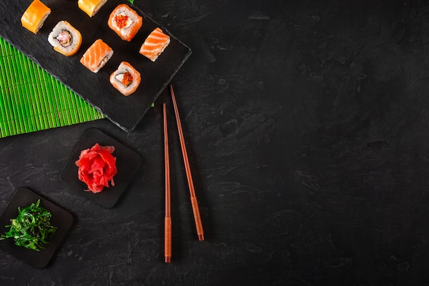 Sushi set di sashimi e involtini di sushi serviti su ardesia di pietra