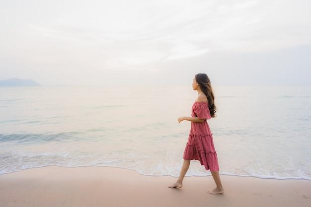 Svago felice di sorriso della bella giovane donna asiatica del ritratto sul mare e sull'oceano della spiaggia