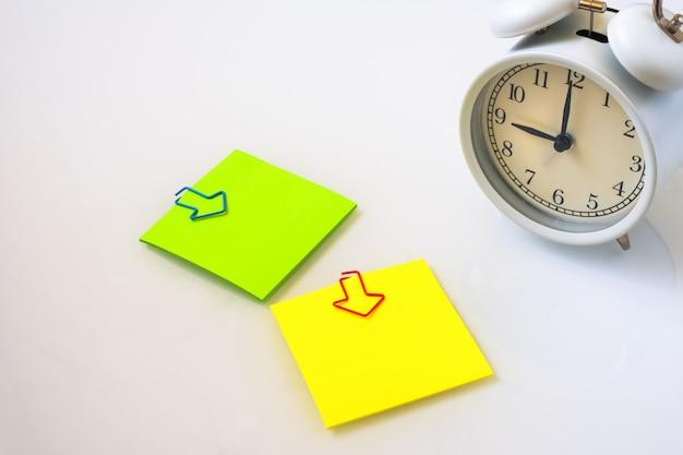 Sveglia bianca e note appiccicose variopinte su una tavola bianca. il concetto di orario di lavoro. posto di lavoro