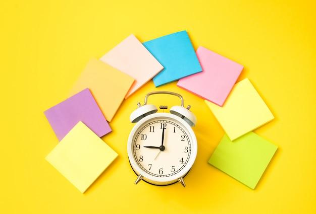 Sveglia bianca e note appiccicose variopinte su una tavola gialla. il concetto di orario di lavoro. posto di lavoro