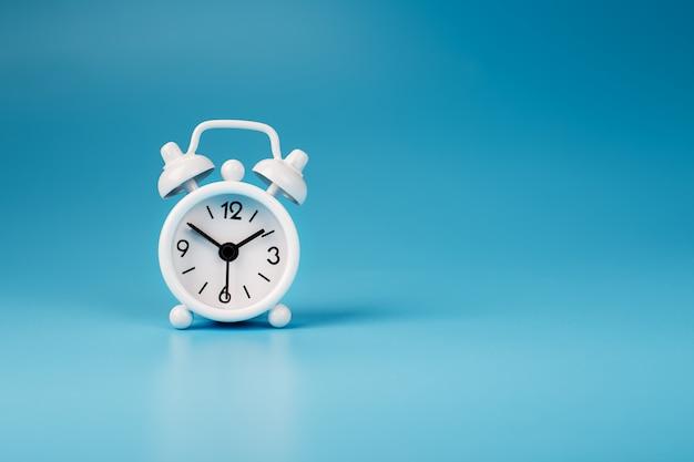 Sveglia bianca su sfondo blu 13-50. concetto di tempo con spazio libero per il testo.