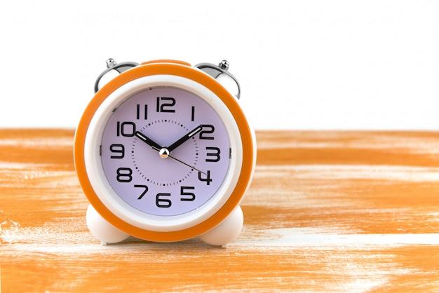 Sveglia bianca su un tavolo di legno arancione