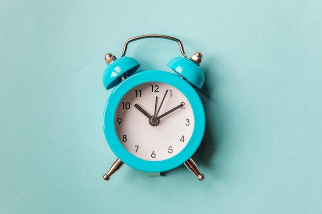 Sveglia classica d'annata della campana gemellata di squillo isolata su fondo d'avanguardia variopinto pastello blu. ore di riposo tempo di vita buongiorno notte sveglia concetto sveglio