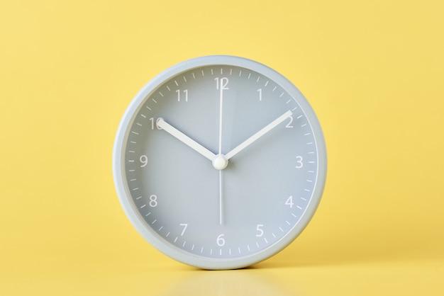 Sveglia classica grigia su una superficie di giallo pastello, fine su