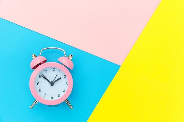Sveglia classica suoneria a campana gemella isolata sulla parete geometrica variopinta pastello rosa giallo blu. ore di riposo tempo di vita buongiorno notte sveglia concetto sveglio. vista dall'alto.