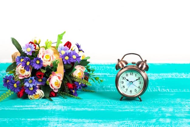 Sveglia con cesto di fiori su legno