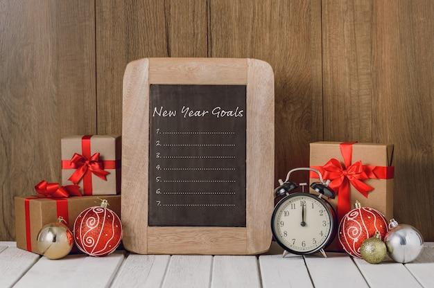 Sveglia con gli ornamenti di natale e la lista degli obiettivi del nuovo anno scritti sulla lavagna sopra fondo di legno