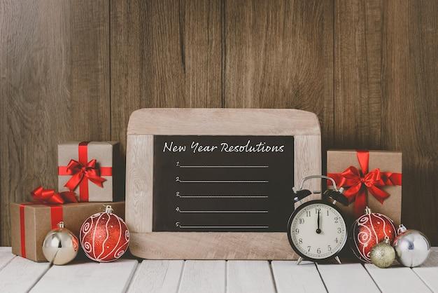 Sveglia con gli ornamenti di natale e la lista delle risoluzioni del nuovo anno scritta sulla lavagna sopra fondo di legno