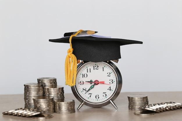 Sveglia con il cappello di graduazione e la pila di soldi delle monete su fondo bianco, soldi di risparmio per il concetto di istruzione
