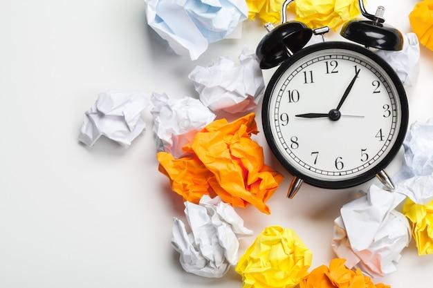Sveglia con le palle di carta sgualcite concetto di idea di pensiero e di pensiero.