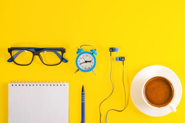 Sveglia, cuffie, occhiali e taccuino blu con la penna, su fondo giallo. tazza di caffè.