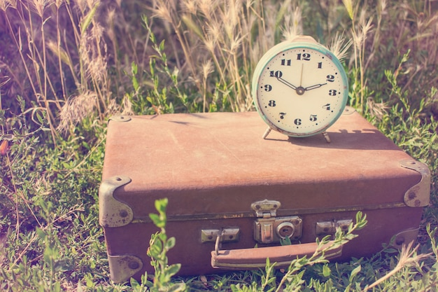 Sveglia d'annata su una vecchia valigia di cuoio marrone classica su un fondo di erba verde.