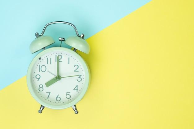 Sveglia dell'annata sulla vista superiore della carta colorata pastello dolce, sulla struttura del fondo, sul colore rosa, porpora, giallo, beige, verde e blu.